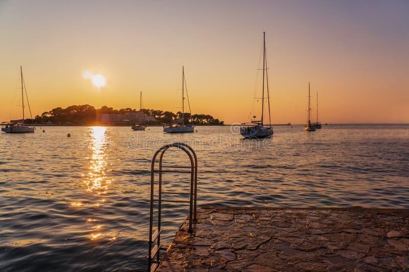 Piękne zmierzchu żeglowania i widoków łodzie obok spławowej pływackiej platformy w Adriatyckim morzu croatia porec zdjęcia stock