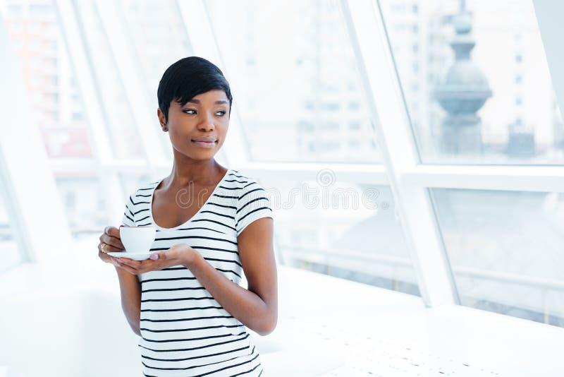 Pięknego amerykanina afrykańskiego pochodzenia bizneswomanu młoda pozycja i pić kawa zdjęcia stock