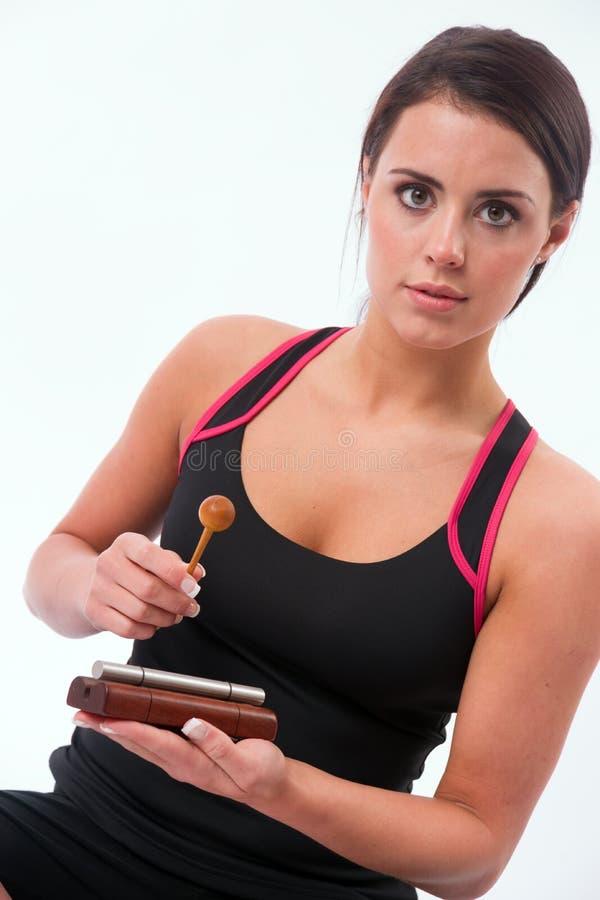 Pięknego brunetki kobiety Uderzającego drewna brzmienia Pojedynczy Chime zdjęcia stock