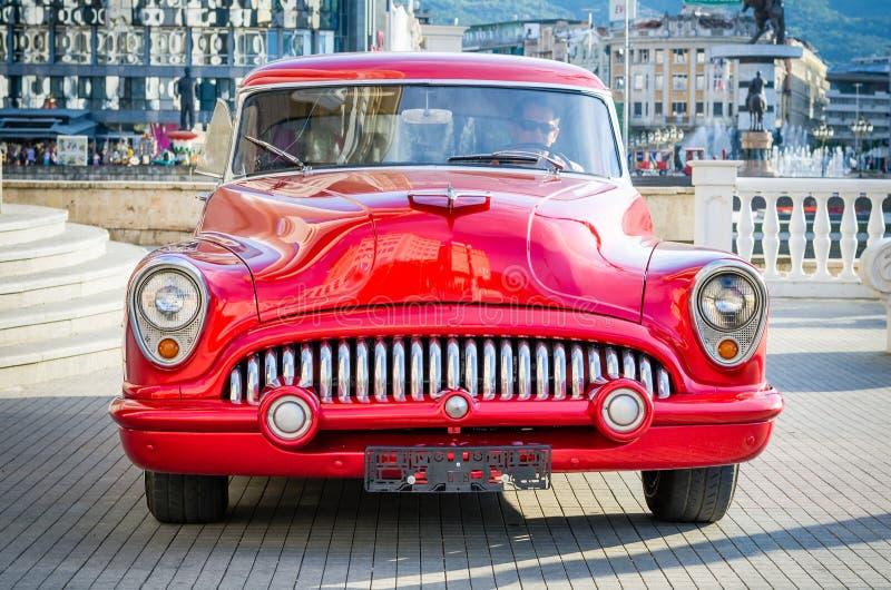 Pięknego czerwonego rocznika zegaru stary samochód od lata sześćdziesiąte w centrum miasta obrazy royalty free