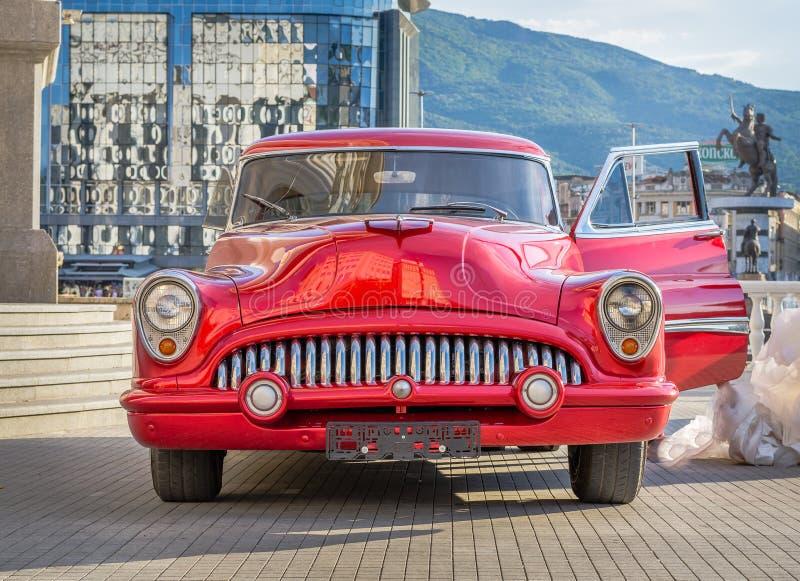 Pięknego czerwonego rocznika zegaru stary samochód od lata sześćdziesiąte w centrum miasta zdjęcia royalty free