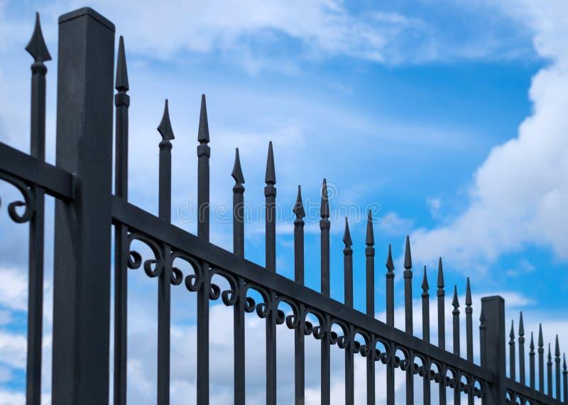 Pięknego dekoracyjnego lanego metalu dokonany ogrodzenie przeciw niebieskiemu niebu Żelazny poręczówki zakończenie up zdjęcie royalty free