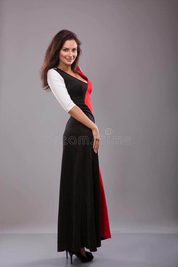 Pięknego dziewczyna wieczór długa suknia pozuje przeciw szaremu tłu zdjęcie royalty free