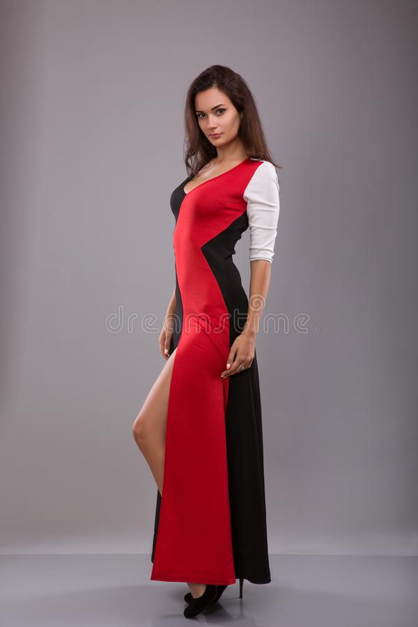 Pięknego dziewczyna wieczór długa suknia pozuje przeciw szaremu tłu obraz royalty free