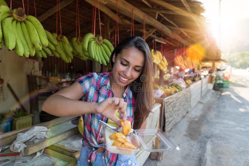 Pięknego dziewczyny łasowania Egzotyczne owoc Na Tradycyjnym Ulicznego rynku Szczęśliwym Uśmiechniętym Atrakcyjnym Żeńskim turyśc obrazy royalty free