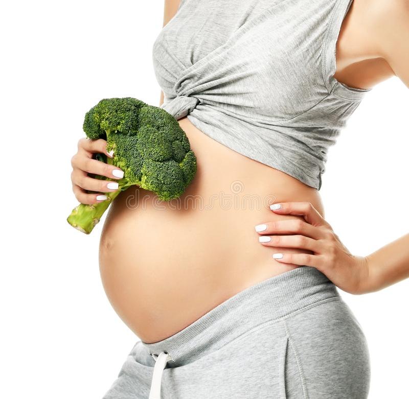 Pięknego kobieta w ciąży brzucha mienia brokułów macierzyństwa dużego Ciążowego oczekiwania zdrowy łasowanie zdjęcie royalty free