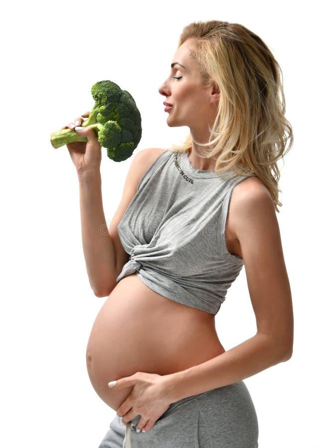 Pięknego kobieta w ciąży brzucha mienia brokułów macierzyństwa dużego Ciążowego oczekiwania zdrowy łasowanie zdjęcia royalty free