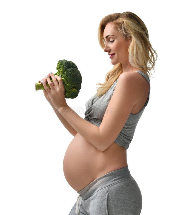 Pięknego kobieta w ciąży brzucha mienia brokułów macierzyństwa dużego Ciążowego oczekiwania zdrowy łasowanie obraz royalty free