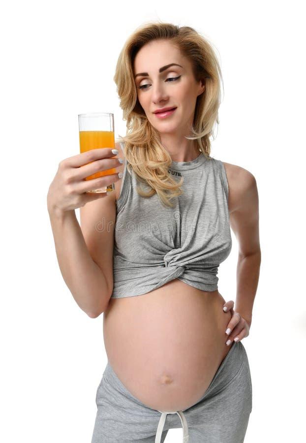 Pięknego kobieta w ciąży chwyta świeży sok pomarańczowy w ręce przygotowywającej pić Ciążowego macierzyństwa oczekiwania zdrowy ł zdjęcia stock