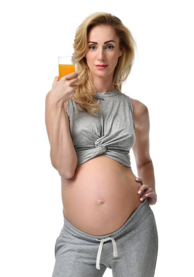 Pięknego kobieta w ciąży chwyta świeży sok pomarańczowy w ręce przygotowywającej pić Ciążowego macierzyństwa oczekiwania zdrowy ł obraz royalty free