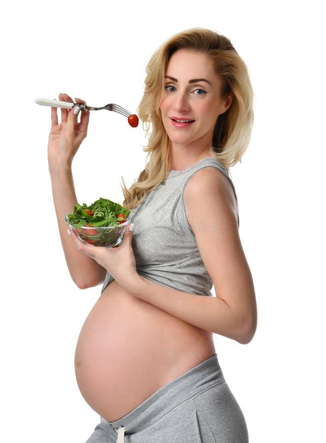 Pięknego kobieta w ciąży chwyta organicznie sałatka i rozwidlenie z pomidorem Ciążowego macierzyństwa oczekiwania zdrowy łasowani fotografia royalty free