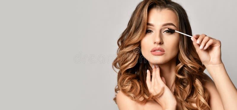 Pięknego kobiety beautician cosmetologist chwyta rzęsy szczęśliwy uśmiechnięty muśnięcie na szarość zdjęcie stock