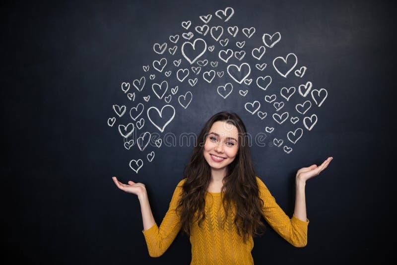Pięknego kobiety mienia rysunkowi serca na palmach nad blackboard obraz stock