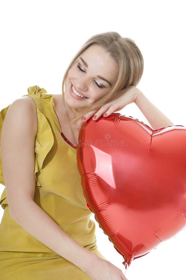Pięknego kobiety mienia serca czerwony balon nad białym tłem. fotografia royalty free