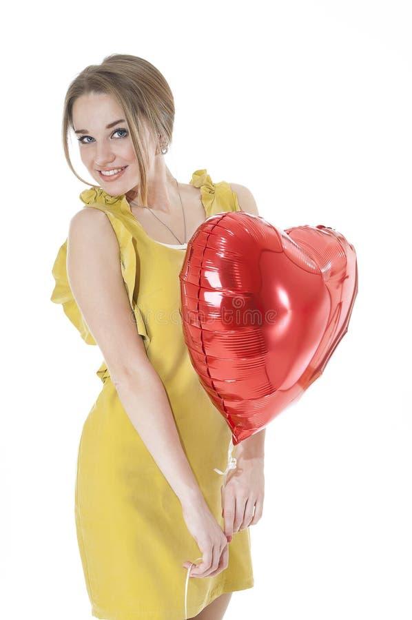 Pięknego kobiety mienia serca czerwony balon nad białym tłem. obrazy stock
