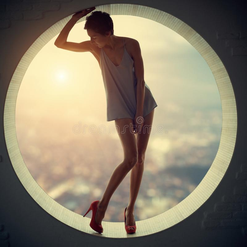 Pięknego młodego dorosłego schudnięcia ładna i atrakcyjna zmysłowości kobieta w eleganci modnej sukni w round okno fotografia stock