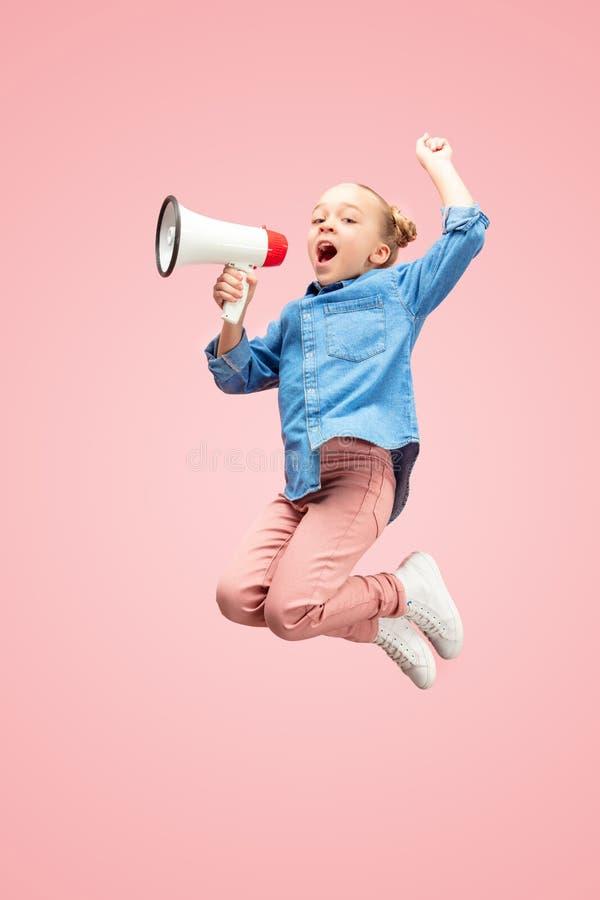 Pięknego młodego dziecka dziewczyny nastoletni doskakiwanie z megafonem odizolowywającym nad różowym tłem zdjęcie royalty free