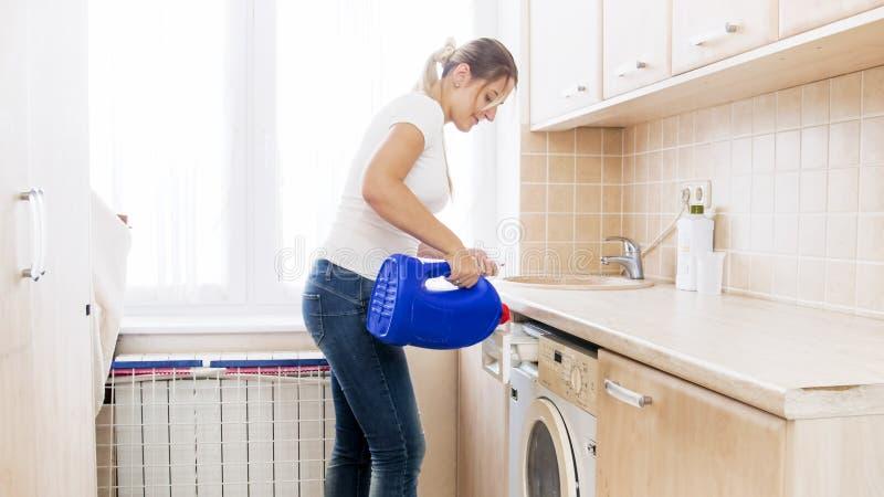 Pięknego młodej kobiety dolewania ciekły płuczkowy proszek w pralce przy pralnią fotografia stock