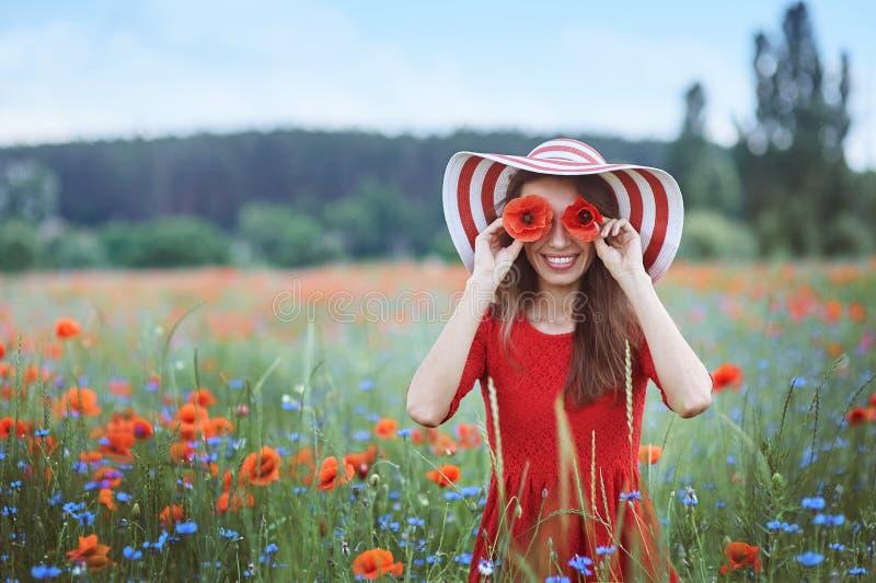 Pięknego młodej kobiety mienia czerwoni maczki przed jej oczami i pozycja w kwiat łące fotografia stock