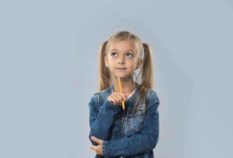 Pięknego mała dziewczynka chwyta Ołówkowy Writing Myśleć Poważny Patrzeć Kopiować przestrzeń Odizolowywającą zdjęcie royalty free