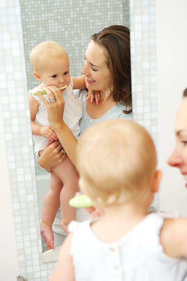 Pięknego macierzystego nauczania śliczny dziecko dlaczego szczotkować zęby obraz stock