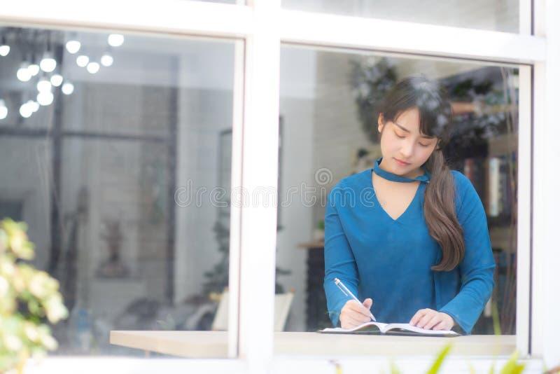 Pięknego portreta Asia kobiety młody pisarz pisze na notatniku lub dzienniczku z szczęśliwym obrazy royalty free