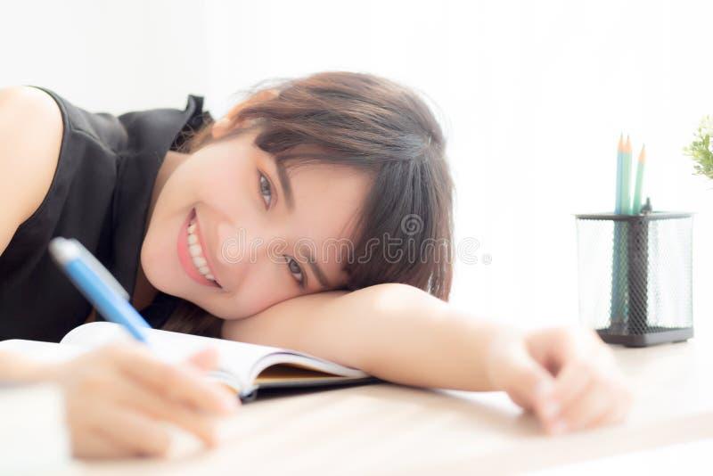 Pięknego portreta kobiety młody azjatykci uśmiech, szczęśliwy pisze uczenie egzamin, praca domowa i lying on the beach z biurkiem fotografia stock