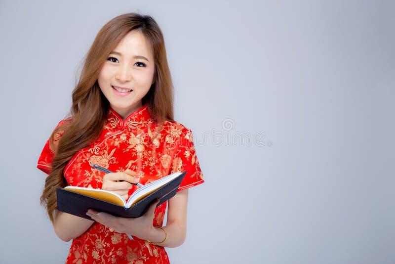 Pięknego portreta kobiety odzieży młody azjatykci czerwony cheongsam pisze notatniku odizolowywającym obrazy stock