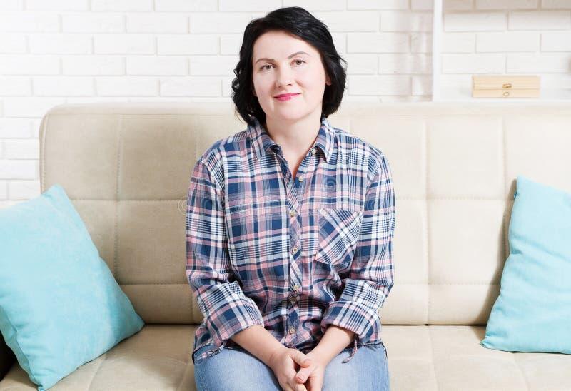 pięknego portreta siedząca kanapy kobieta Atrakcyjny żeński relaksować w domu po ciężkiego dnia obraz royalty free