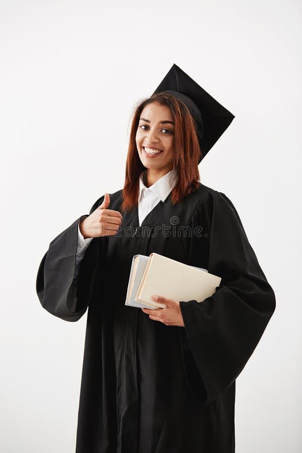 Pięknego szczęśliwego afrykańskiego kobieta absolwenta seansu ok uśmiechnięty mienie rezerwuje patrzeć kamerę obrazy stock