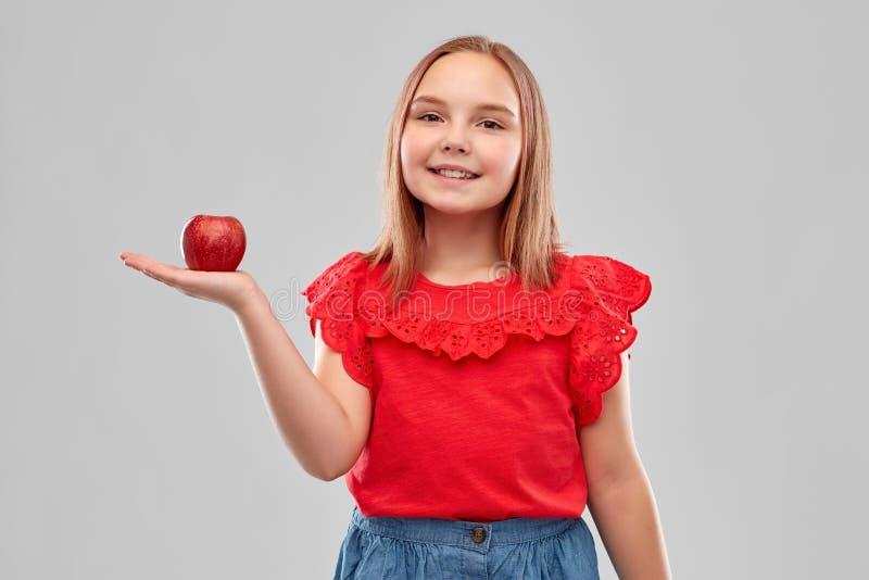 Pięknego uśmiechniętego dziewczyny mienia czerwony jabłko na palmie obraz stock