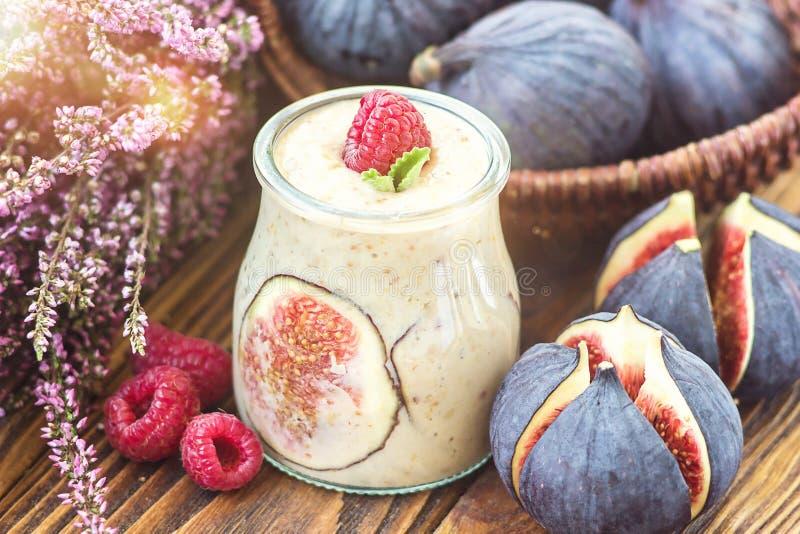 Pięknego zdrowego zakąsek fig owocowego smoothie dojny potrząśnięcie w szklany słój dekorować świeżych figach różowi malinka odgó obrazy royalty free