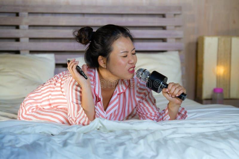 Pięknej Azjatyckiej Amerykańskiej nastolatek dziewczyny śpiewacki karaoke pieśniowy z podnieceniem sypialni mienia telefon komórk zdjęcia stock