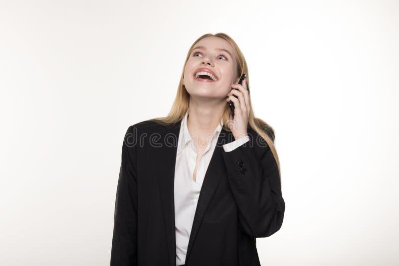 Pięknej blondynki biznesowa dama w czarnym kostiumu opowiada na ono uśmiecha się i telefonie komórkowym obraz royalty free