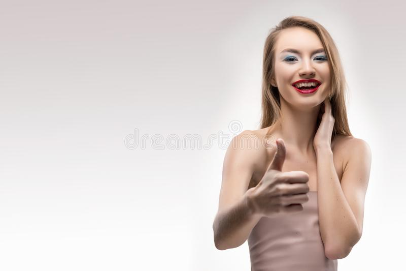 Pięknej blondynki czerwone wargi uśmiecha się dziewczyny pokazują szyldowego kciuk fotografia stock