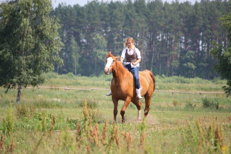 Pięknej blondynki kobiety jeździecki koń jeździecki zdjęcia stock