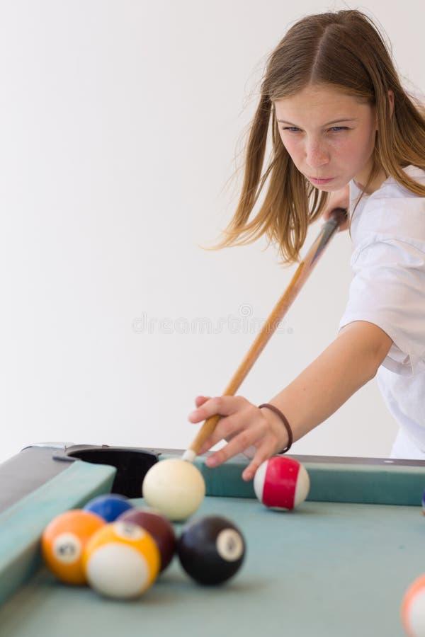 Pięknej blondynki młoda nastoletnia dziewczyna bawić się billard, ogniskowanie i celowanie, piłka zdjęcia royalty free