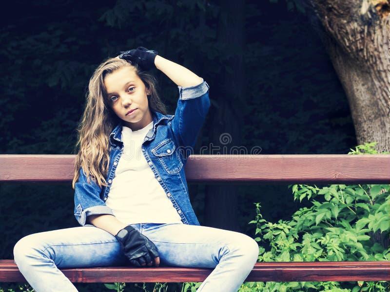Pięknej blondynki nastoletnia dziewczyna w cajg koszula, siedzący na ławce z plecakiem i deskorolka w parku obrazy stock