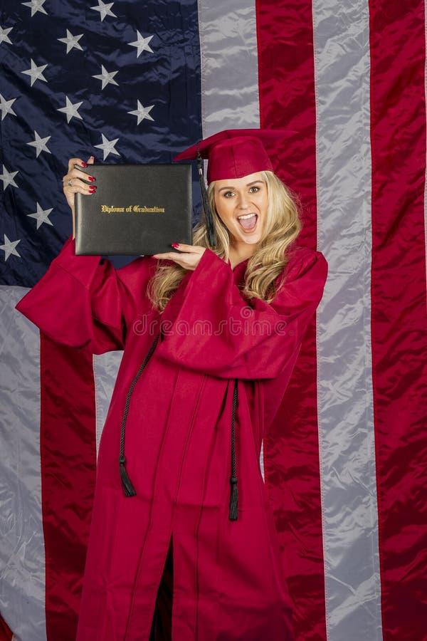 Pięknej blondynki Wzorcowy Pozować Z dyplomem Z flagą amerykańską W tle zdjęcia stock