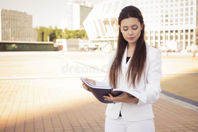 Pięknej brunetki biznesowa kobieta czyta outdoors w białym kostiumu z falcówką dokumenty w jej rękach obraz royalty free