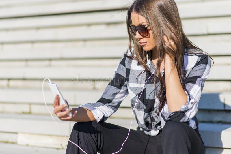 Pięknej brunetki caucasian dziewczyna słucha muzyka z nim obrazy stock