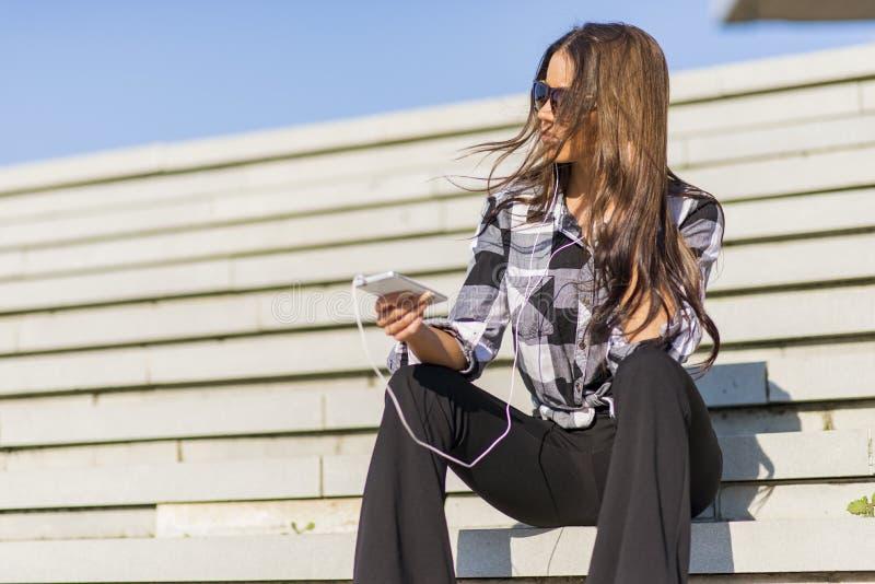 Pięknej brunetki caucasian dziewczyna słucha muzyka z nim zdjęcia stock