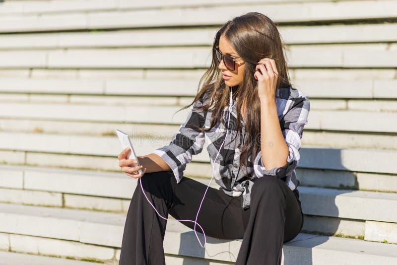 Pięknej brunetki caucasian dziewczyna słucha muzyka z nim obraz stock