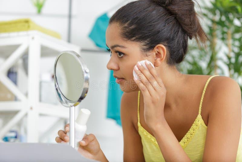 Pięknej brunetki kobiety czyści twarz z bawełnianym ochraniaczem fotografia royalty free