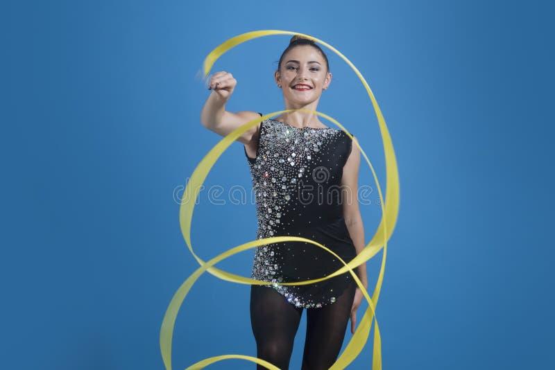 Pięknej brunetki kobiety gimnastyczki calilisthenics stażowy ćwiczenie z faborkiem na pracownianym tle Sztuk gimnastyki zdjęcia stock