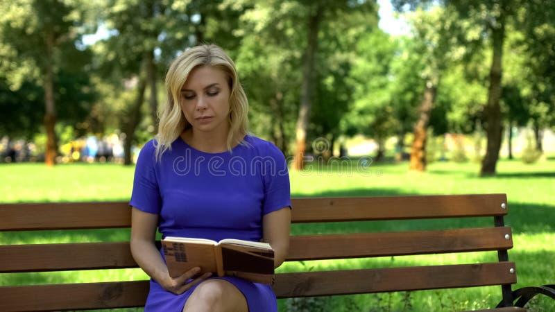 Pięknej damy czytelnicza książka w parku, siedzący na ławce, wydaje czas wolnego, hobby zdjęcia stock