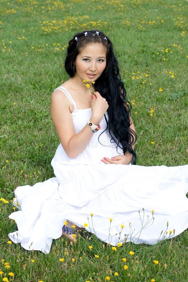 pięknej dziewczyny trawy ciężarny obsiadanie obraz stock