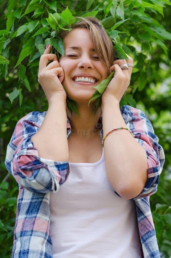 Pięknej dziewczyny uśmiechnięty mienie wręcza liście drzewo obraz stock
