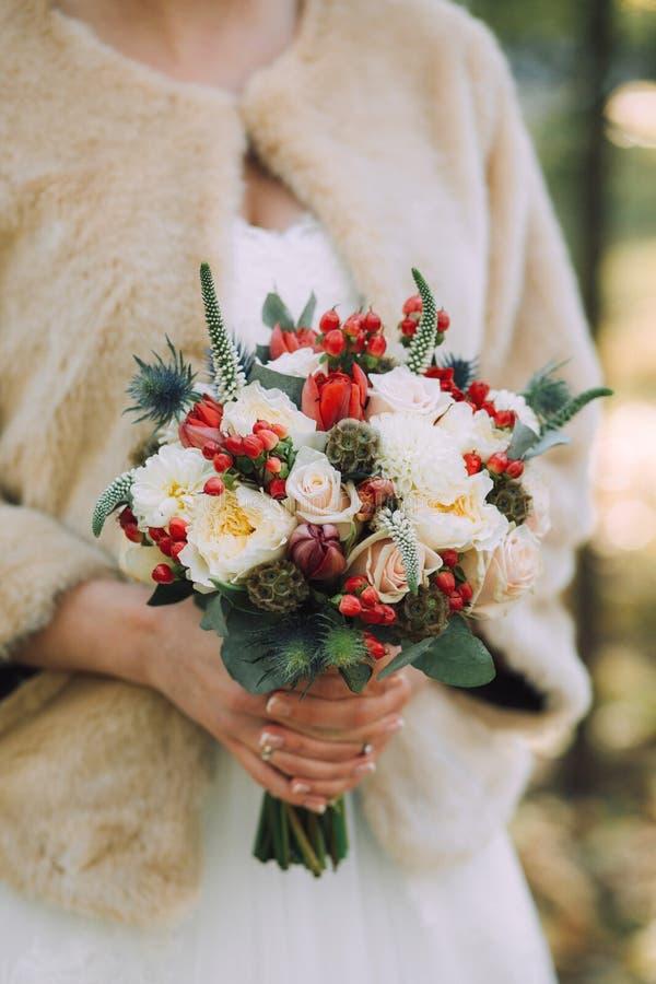 Pięknej eleganckiej jesieni ślubny bukiet białe róże i czerwień kwitnie w rękach panna młoda wewnątrz w beżowym futerkowym żakiec obrazy royalty free