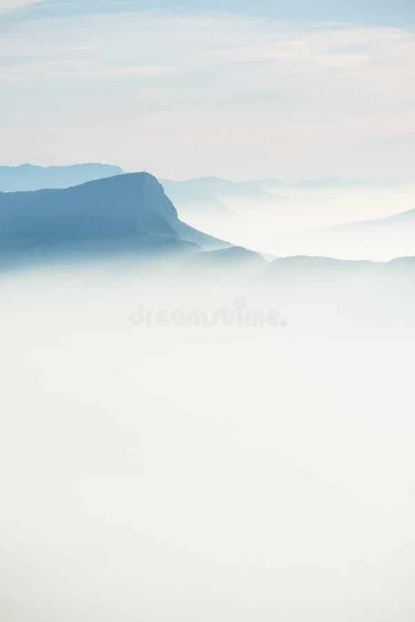 Pięknej francuskiej alps zimy widok z lotu ptaka panoramiczny krajobraz z fantastycznym błękitnej mgiełki chmurnym halnym tłem fotografia stock